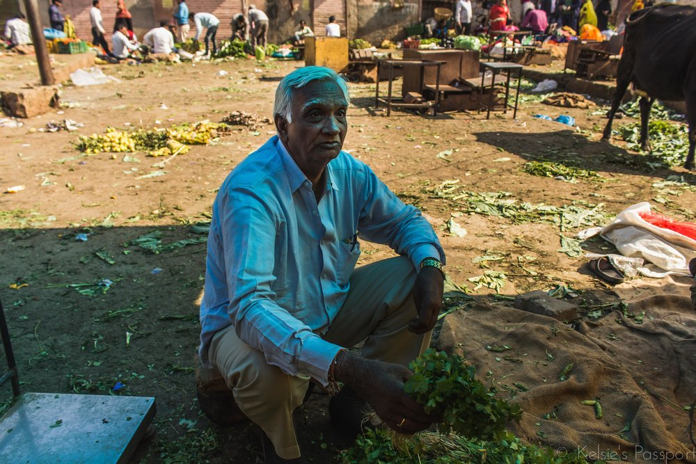 A man sits on the remnants of the morning market with his unsold greens.