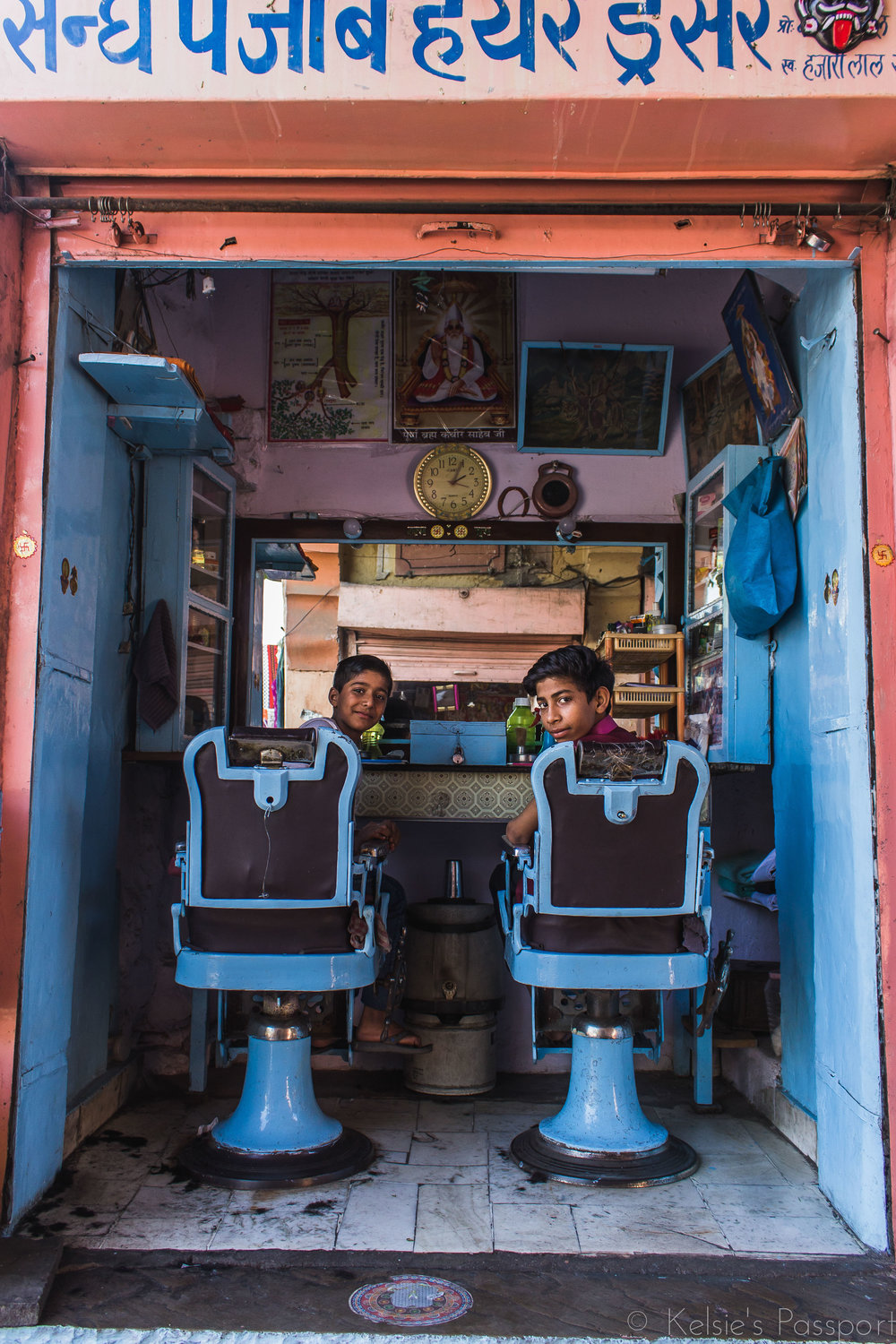 Two boys take advantage of no customers in a barber shop.