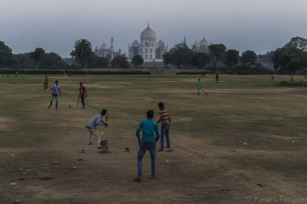 An evening game of cricket on a pitch with a view of the famous Taj Mahal, Agra.