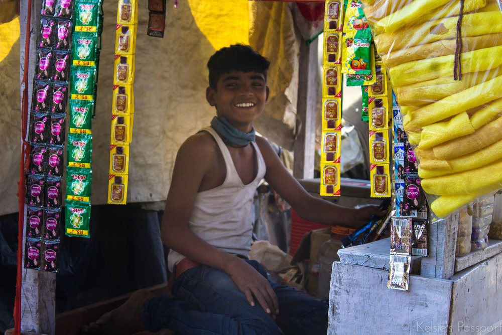 A boy working his stall on the edge of his slum.