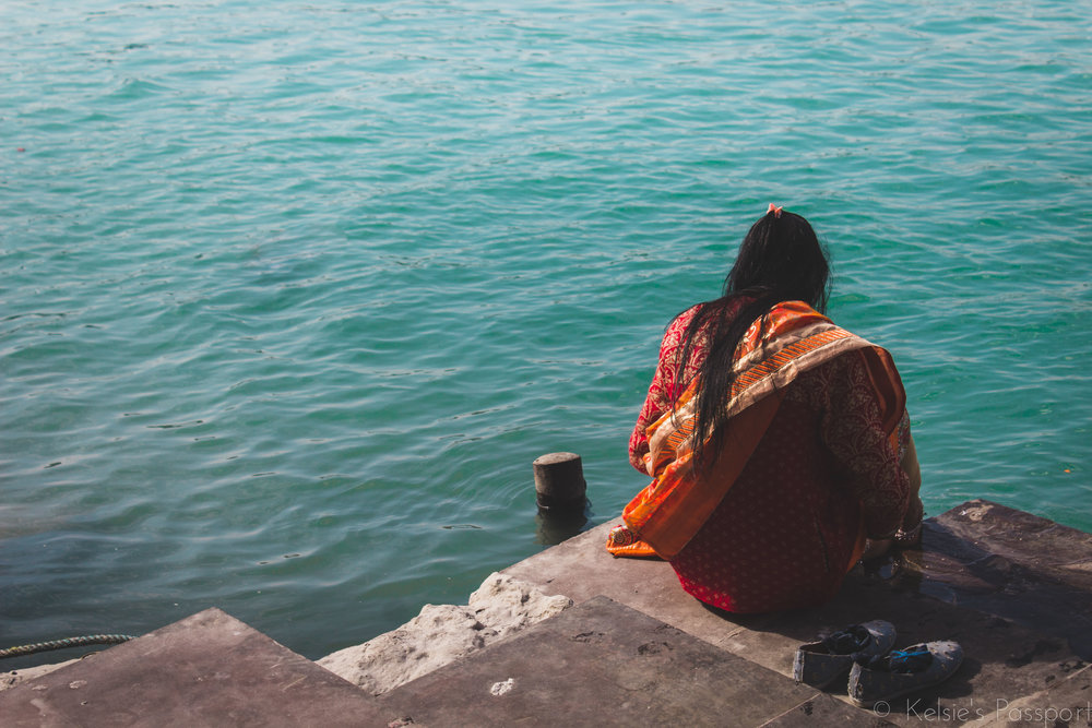 A woman sits on the edge of the river Ganges.