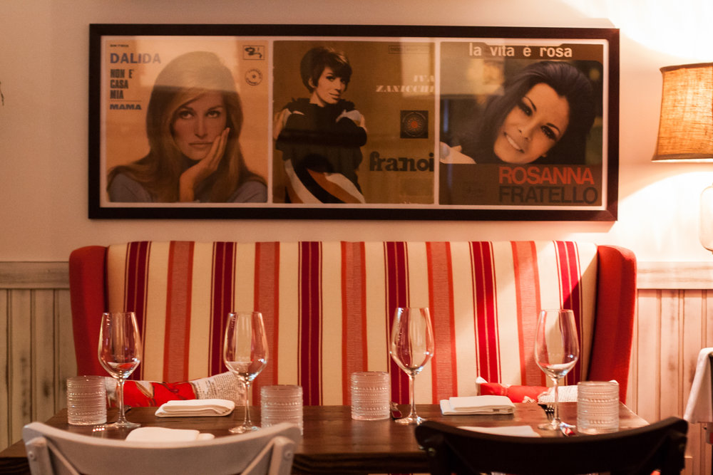 Cozy loveseats and vintage '60s Italian record covers adorn the Claudia Room.