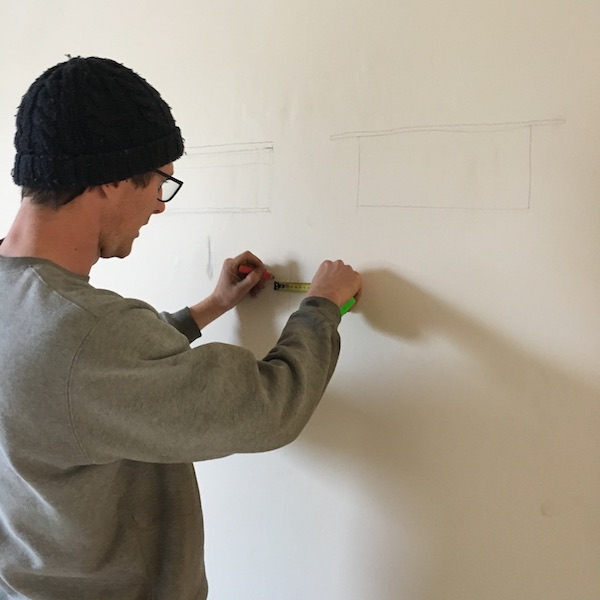 Planning the furniture. He always liked drawing on the walls.