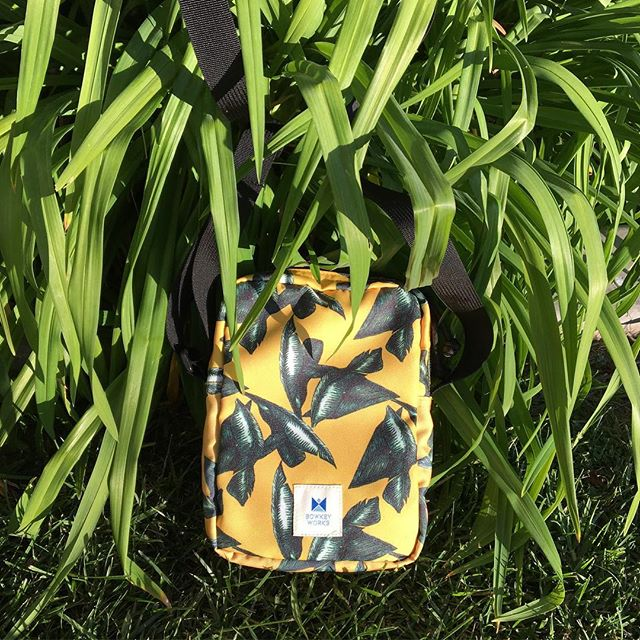 Our Golden Tropics crossbody bag in the wild.  Great for carrying your phone, wallet, snacks & much more.  Large main compartment, inner & outer back mesh pockets with a clean minimalistic look.  Fabric was printed in-house in California by us and all our bags are handcrafted in USA. 🌴✨😎
