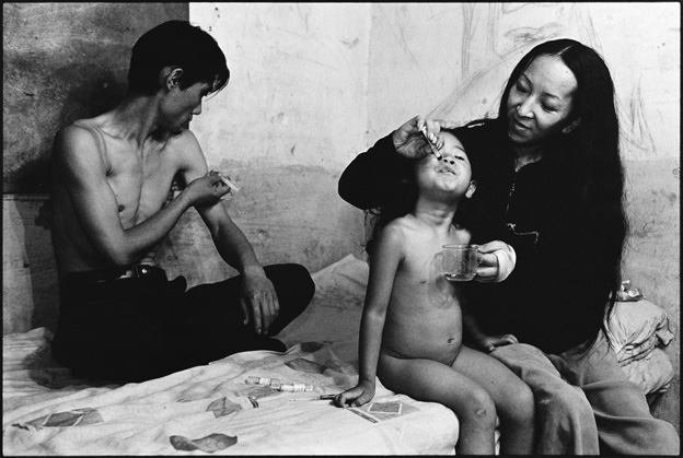 A Father Injecting Heroin and a Mother Feeding Her Daughter Heroin
