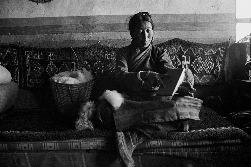 A woman combing wool, Tibet