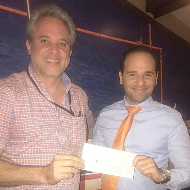 Edgar Lomba recibiendo de Leonardo Ferrand, cheque de patrocinio Ferrand & Oviedo, SRL