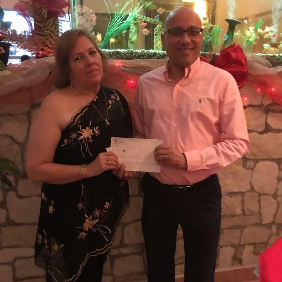 Juan Miguel Madera recibiendo de Sra. Alma Valverde cheque de patrocinio a SND de la empresa de Ingenieros, Henríquez Soñe & Asoc. SRL  Conoce todos nuestro patrocinadores .