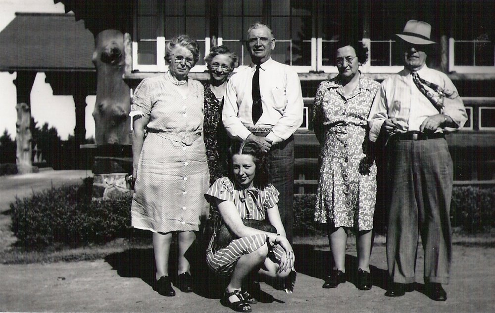 "Left to right standing:  ""Mayme"" Hanley  (Jack's sister),  Lydia Schmidt McNamara  (the sister of my 2nd great grandmother, Fanny Schmidt Ratz),  John ""Jack"" Hanley ,  Alma Ratz Hanley  (Jack's sister-in-law and my great grandmother), and  Michael John Hanley  (my great grandfather, Alma's husband). Kneeling is Jack's niece,  Helen Hanley Toups .  [NOTE: Aunt Bev had identified the man far right as her uncle  Peter McNamara  (Lydia's husband), but he looks more like my great grandfather to me. It is hard to tell with his hat and the shadow over his eyes. Either man would have made sense in this picture as both of their wives, Lydia and Alma, are in the photo]"