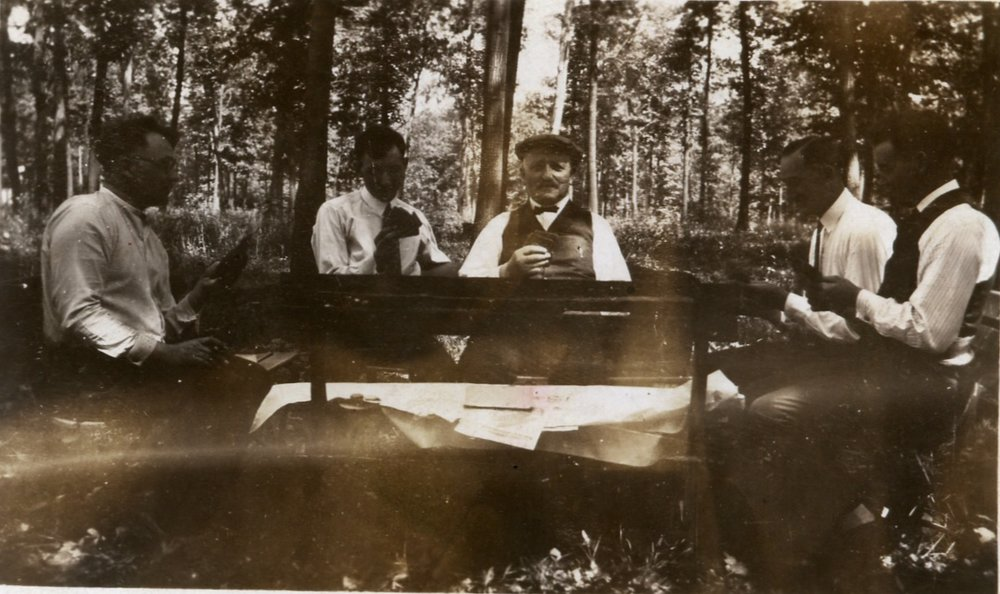 Peter Henry Ratz (center) playing cards with some men in the woods