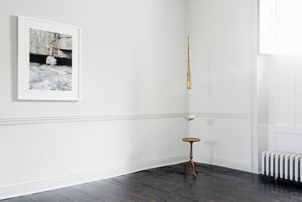 Dorothy Cross – Boulder ,  2014, Archival pigment print, 92.3 x 74.8 cm framed  Dorothy Cross  –   Table Telescope , 2016, Cast iron table 49 x 28 cm, antique brass telescope 5 x 91 cm, gilded human skull, meteorite