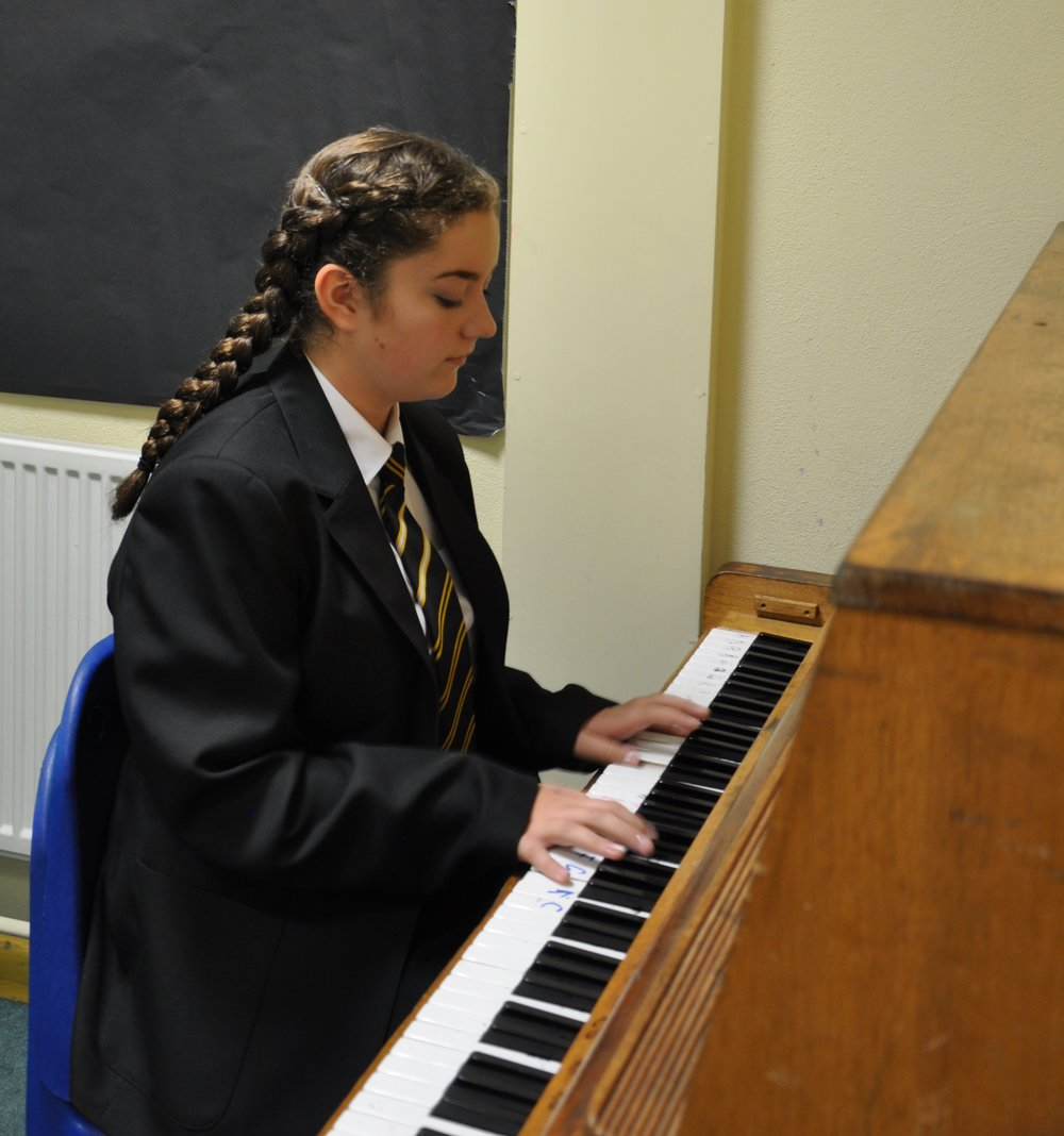 Pool Academy student playing a school piano.