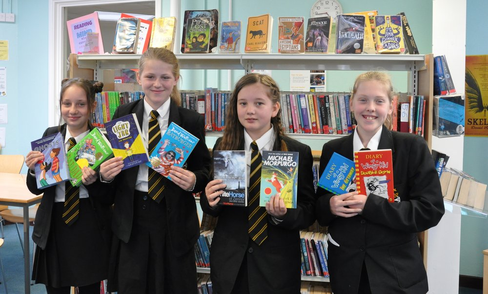 Students holding a selection of the new titles coming soon to the library.