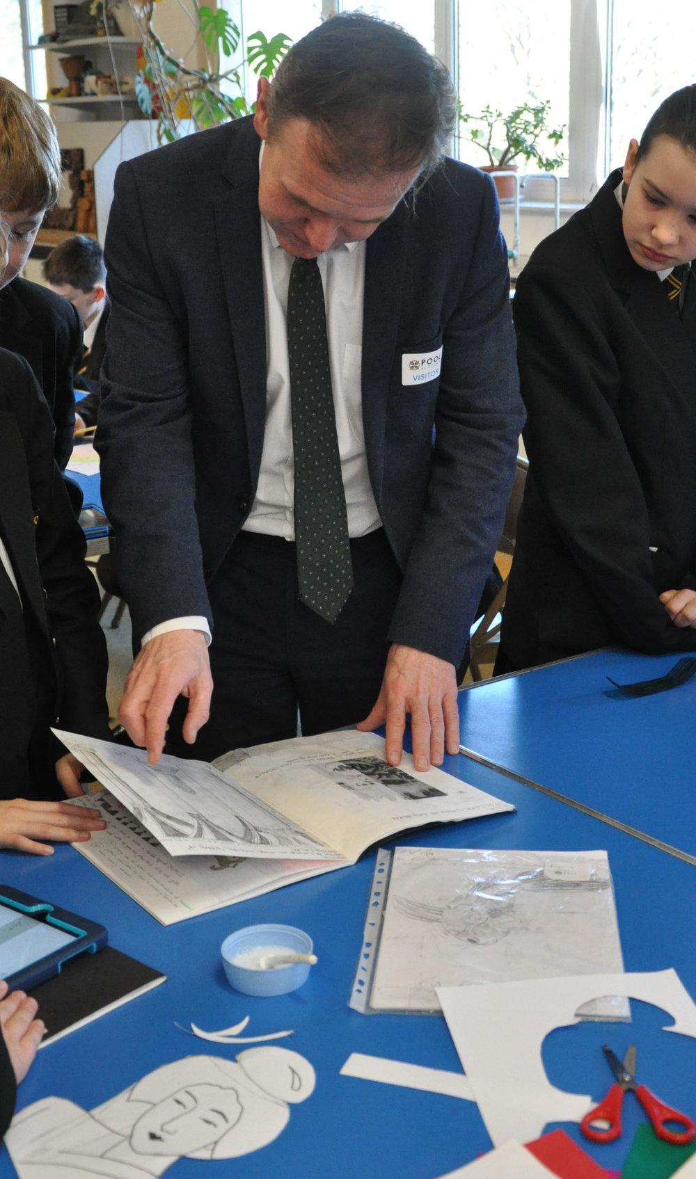 Mr Eustice looking through student's art work.