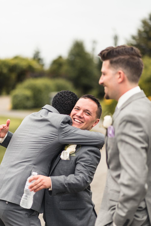 Groom receiving a hug from guest