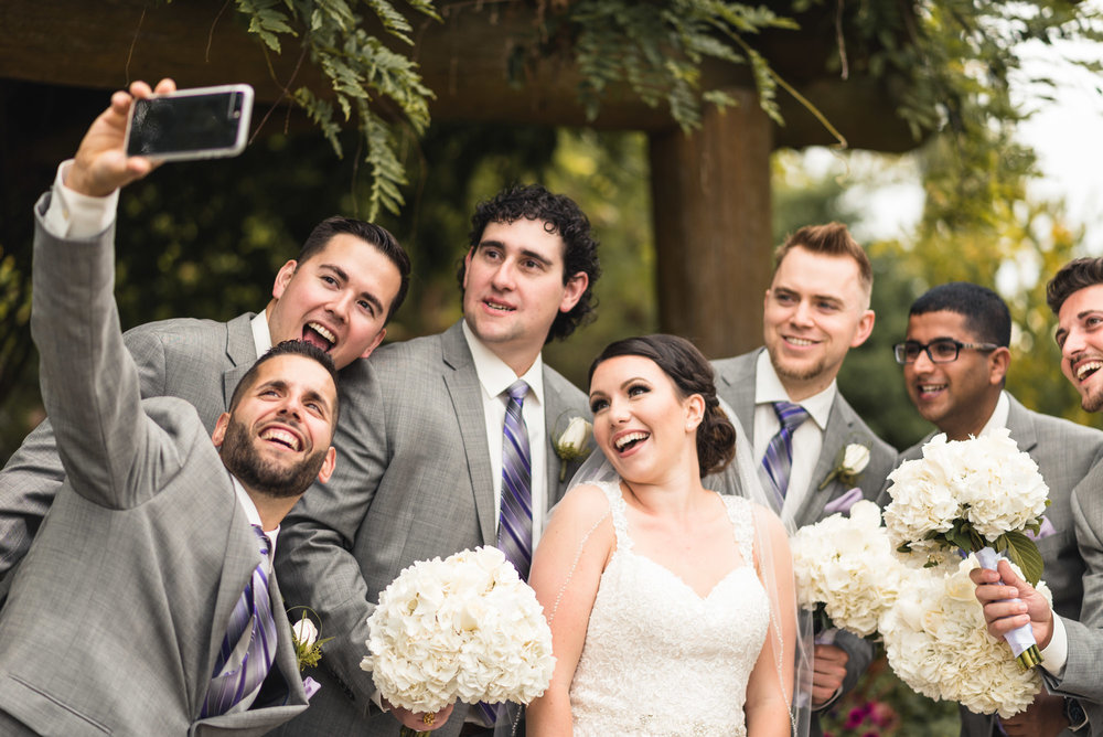 Groomsmen taking selfie with Bride
