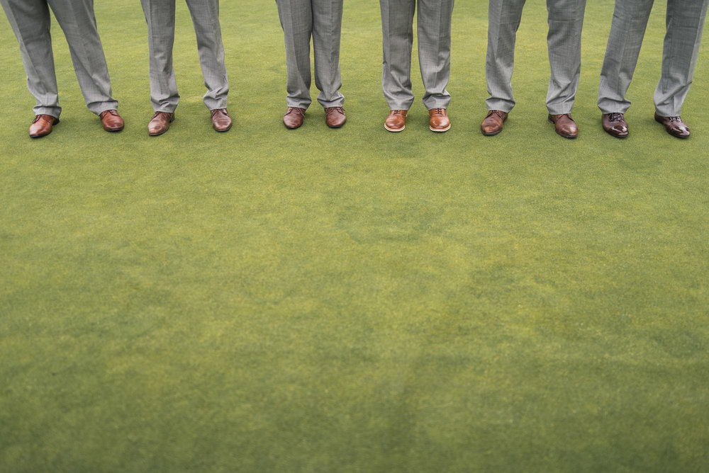Groomsmen brown shoes with grey pants on grass