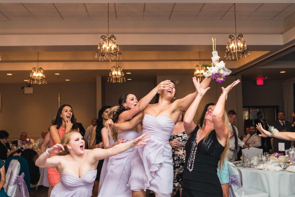Bridesmaid catches bouquet at reception