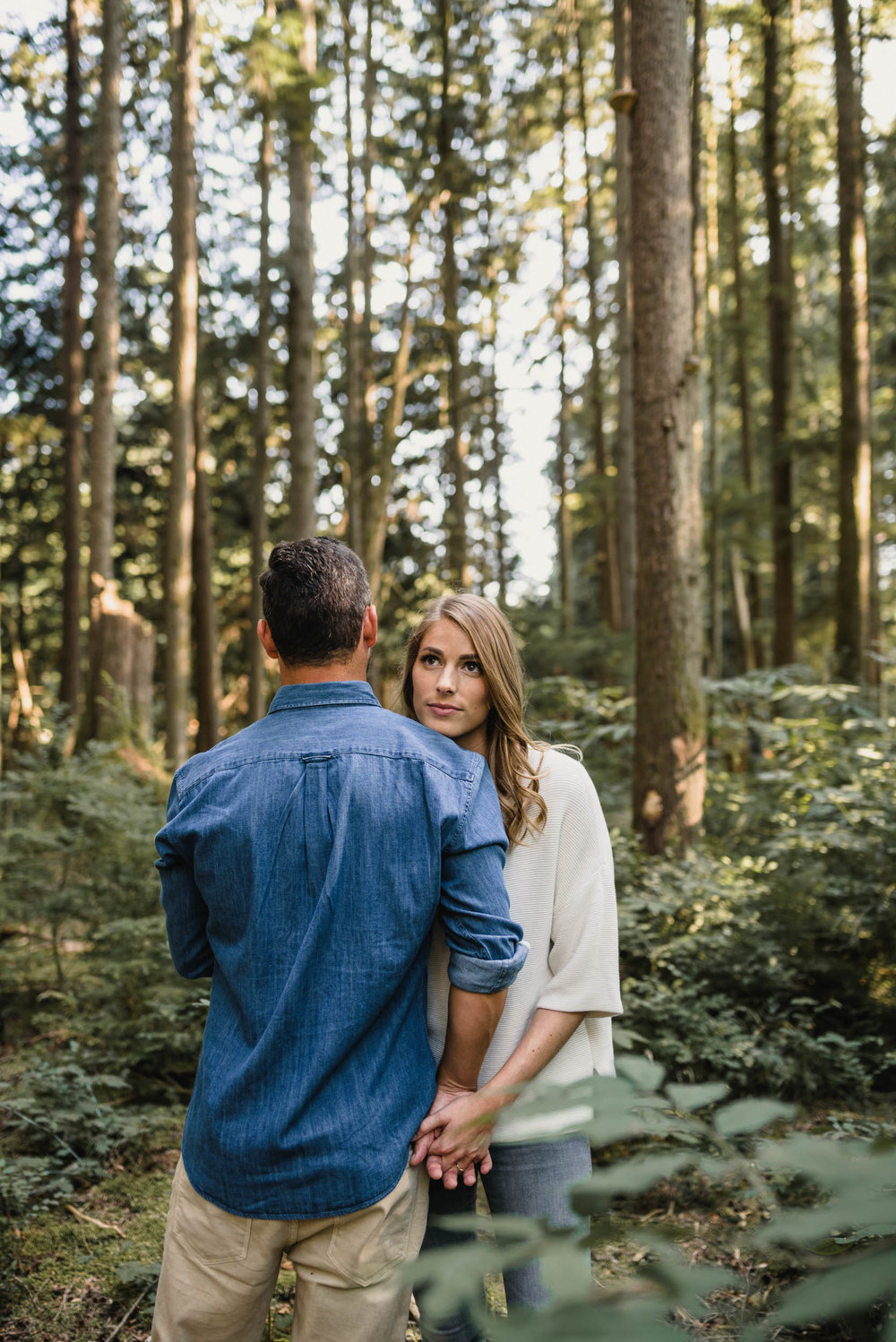 Couple embraces in foliage. Girl looks over guy's shoulder.