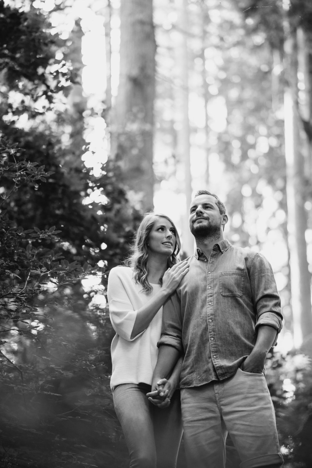 Couple looks off into the distance in the forest