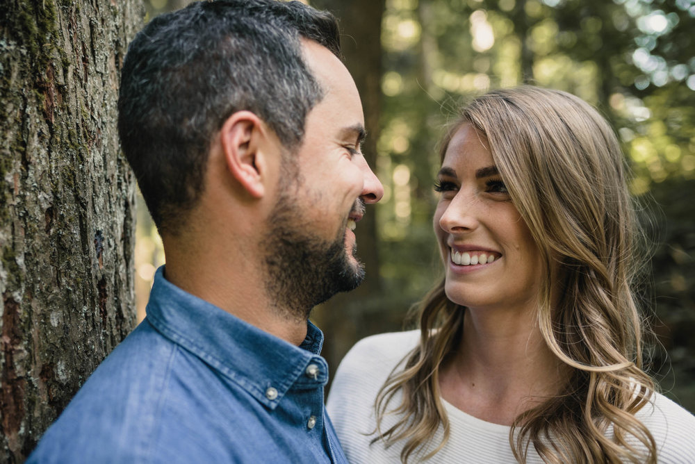 Couple smiles at each other in the forest