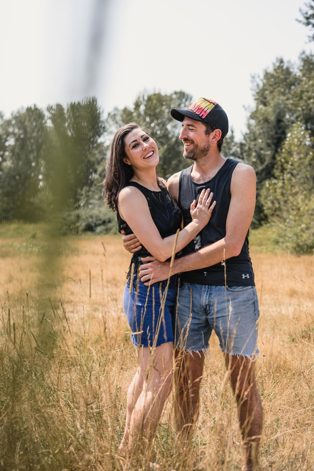 Couple hugging and smiling in field