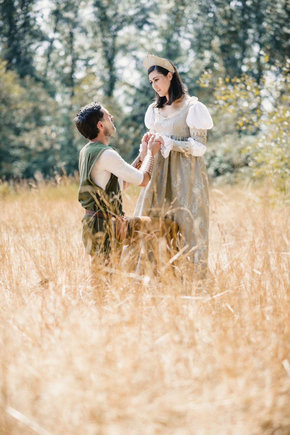 Couple kneeling in field with medieval costumes