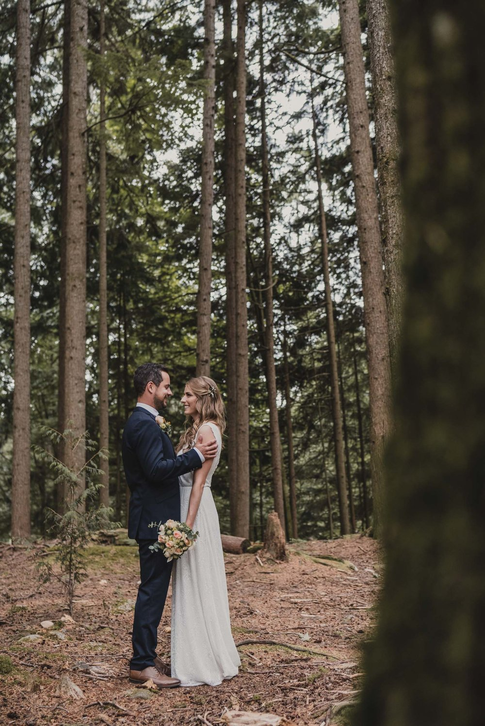 Bride and groom embrace in forest