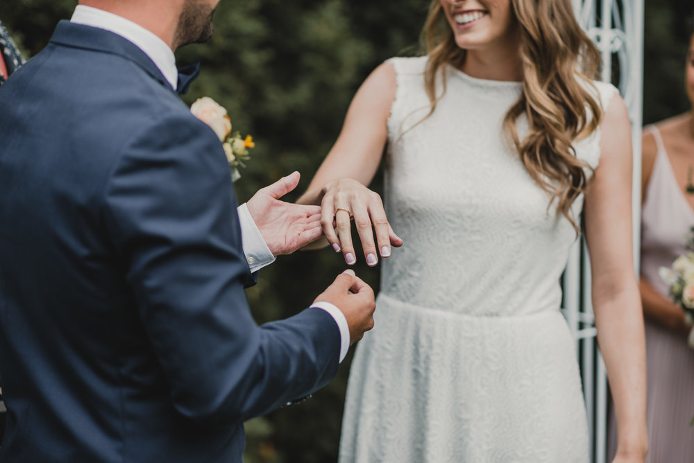 Grooms places ring on Bride's finger