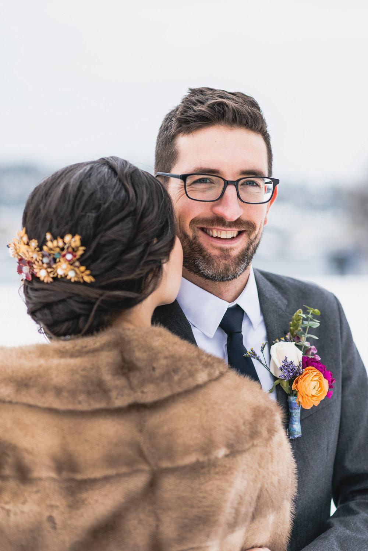 Groom smiles over Bride's shoulder