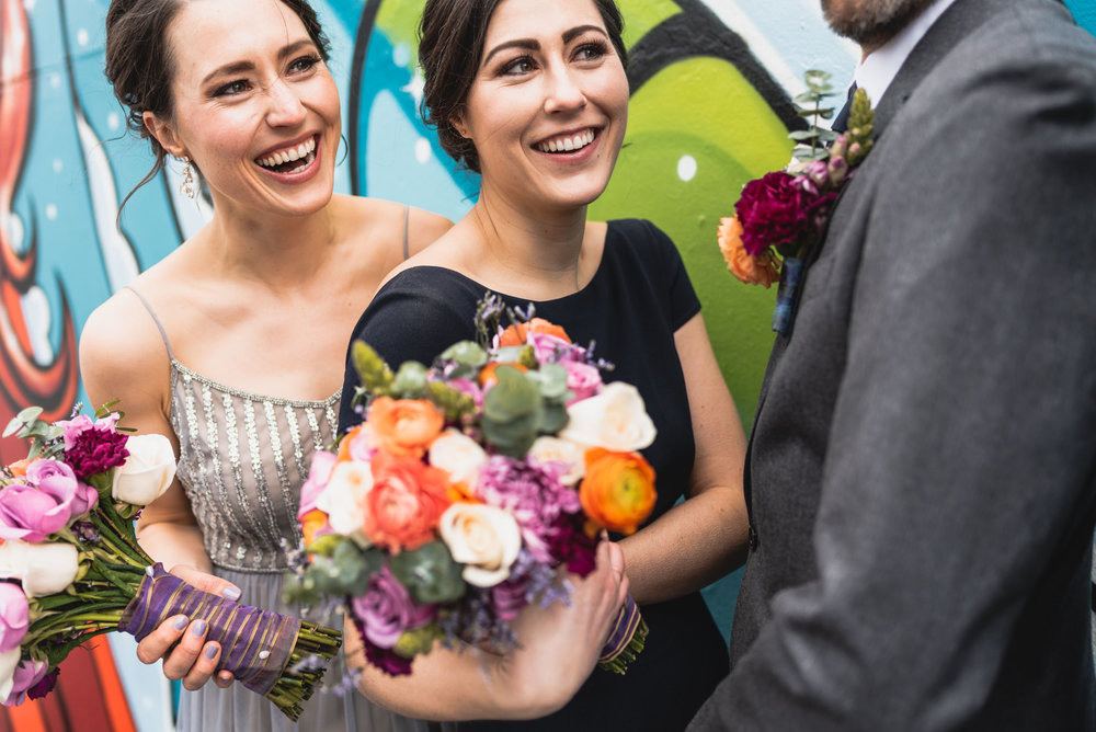Bridal party laughs by mural