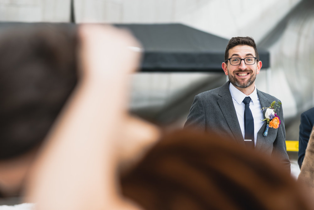 Groom happily watches Bride fix her hair