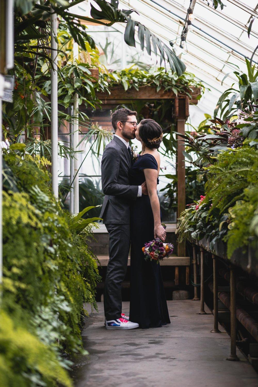Bride and groom kiss among plants