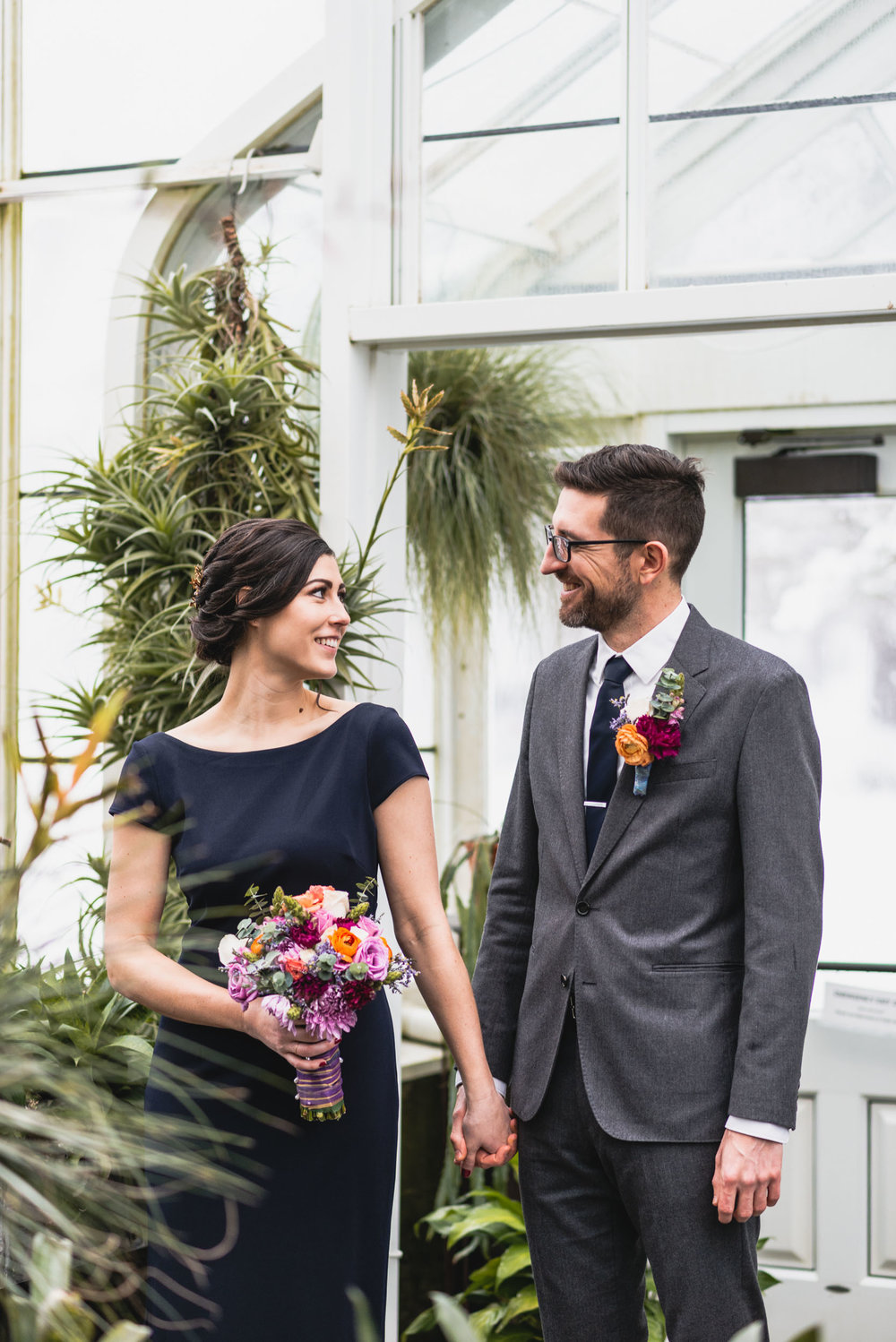 Bride and groom hold hands among plants