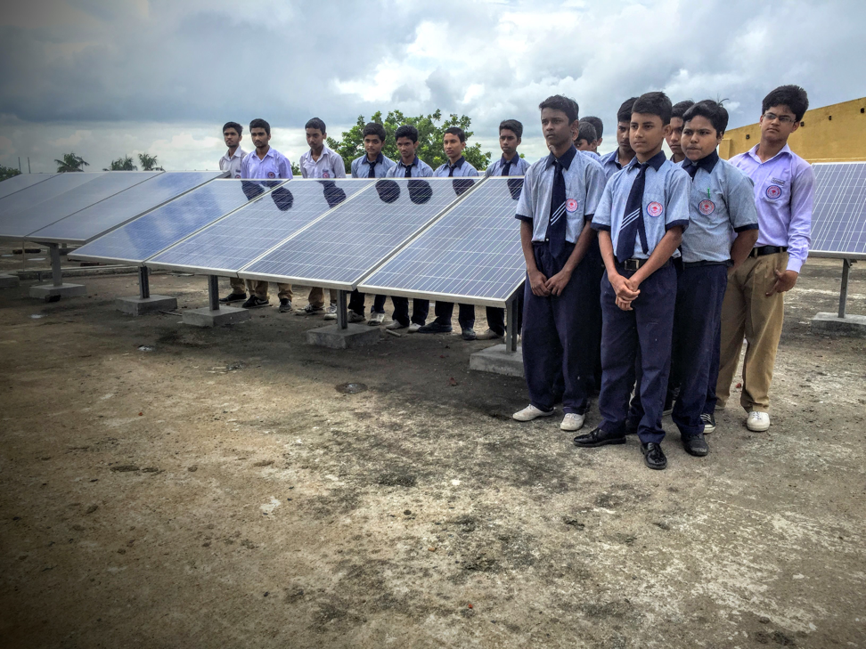 SCHOOL CHILDREN WITH THE NEWLY INSTALLED ROOFTOP SOLAR PANELS AT KHARDAH SIBNATH HIGH SCHOOL.
