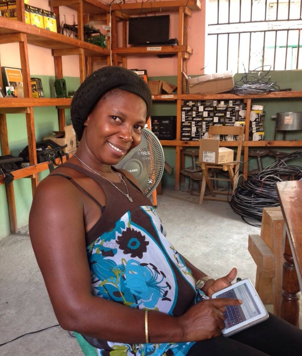 EarthSpark takes a '  feminist electrification'   approach to energy access, intentionally leveraging the arrival of electricity to benefit women. Here, Rosane Jean-Jacques, a grid ambassador, sells electricity credits from a tablet.
