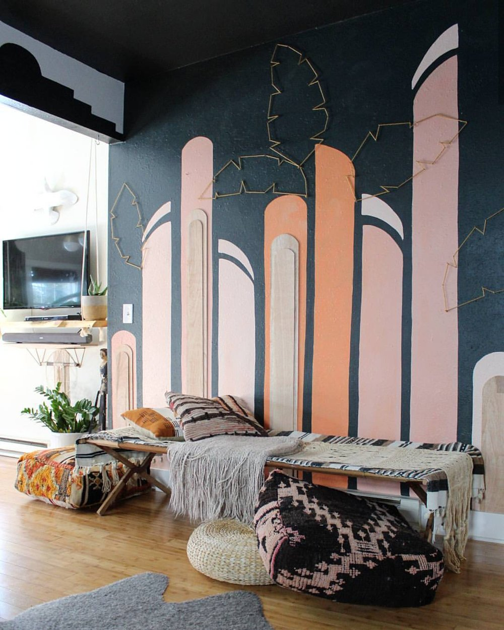 A fun and colorful mural with the addition of plywood shapes and palm leaves made of yarn wrapped around nails.