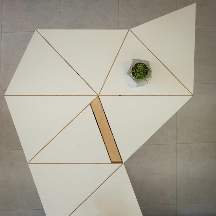 A ideia foi projetar uma grande mesa formada por triângulos, preenchendo os espaços e criando estações de trabalho - GOSTOU DESSA IDEIA?