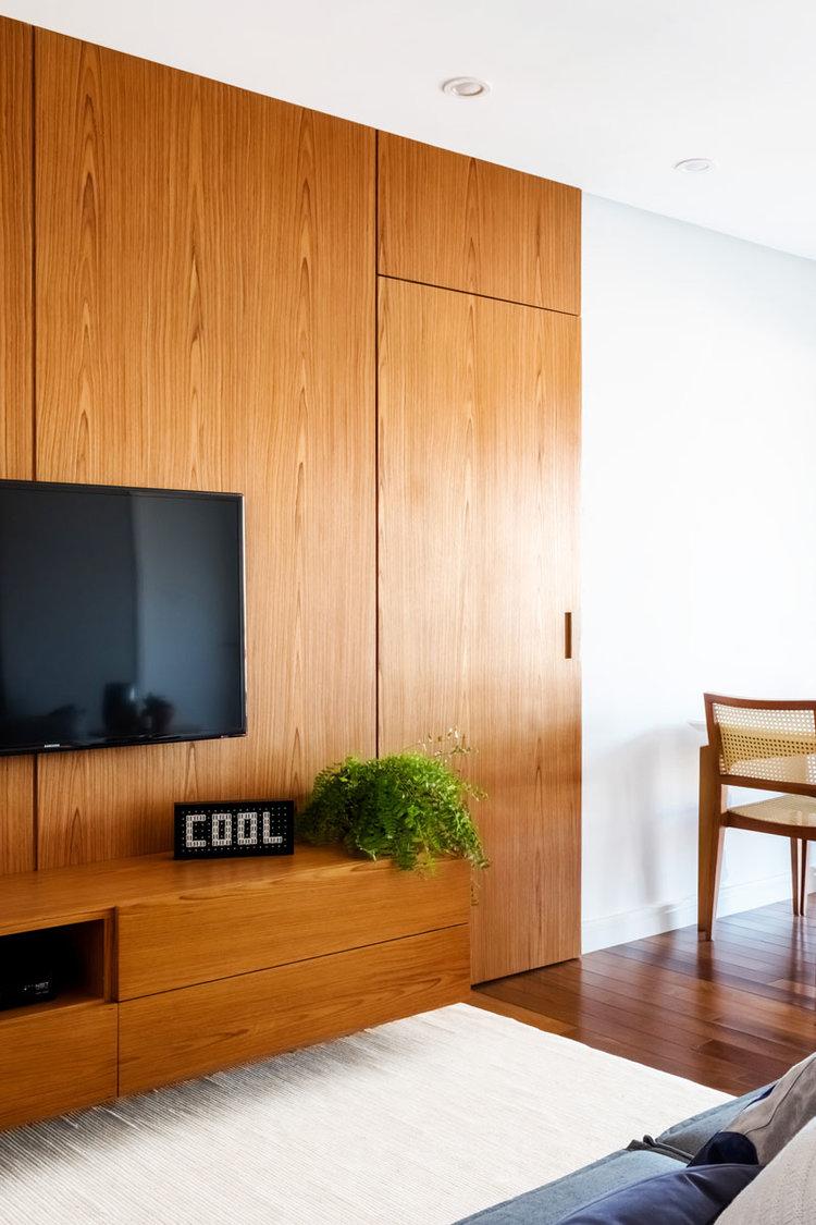 macroarq_arquitetura_interiores_projeto_reforma_apartamento_sao_paulo_sala_de_estar_clara_iluminada_piso_taco_painel_de_madeira_com_porta_embutida_fechada_aparador_de.jpg