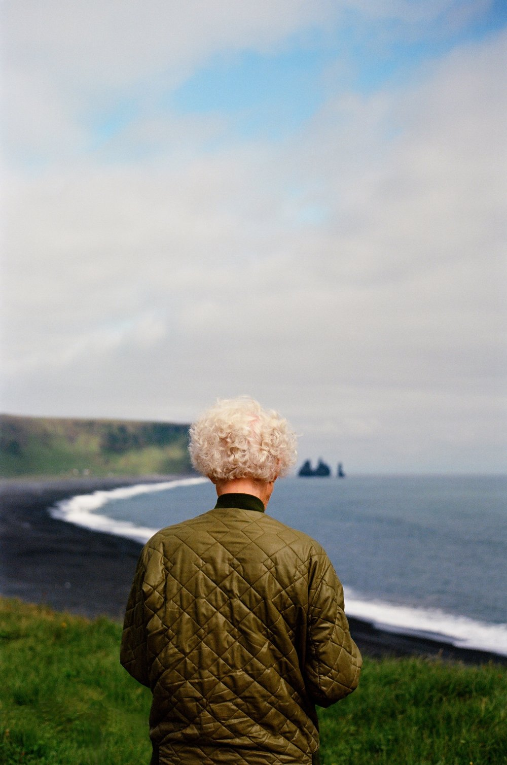 A fellow tourist admires the beauty of Vik's coastline.jpg