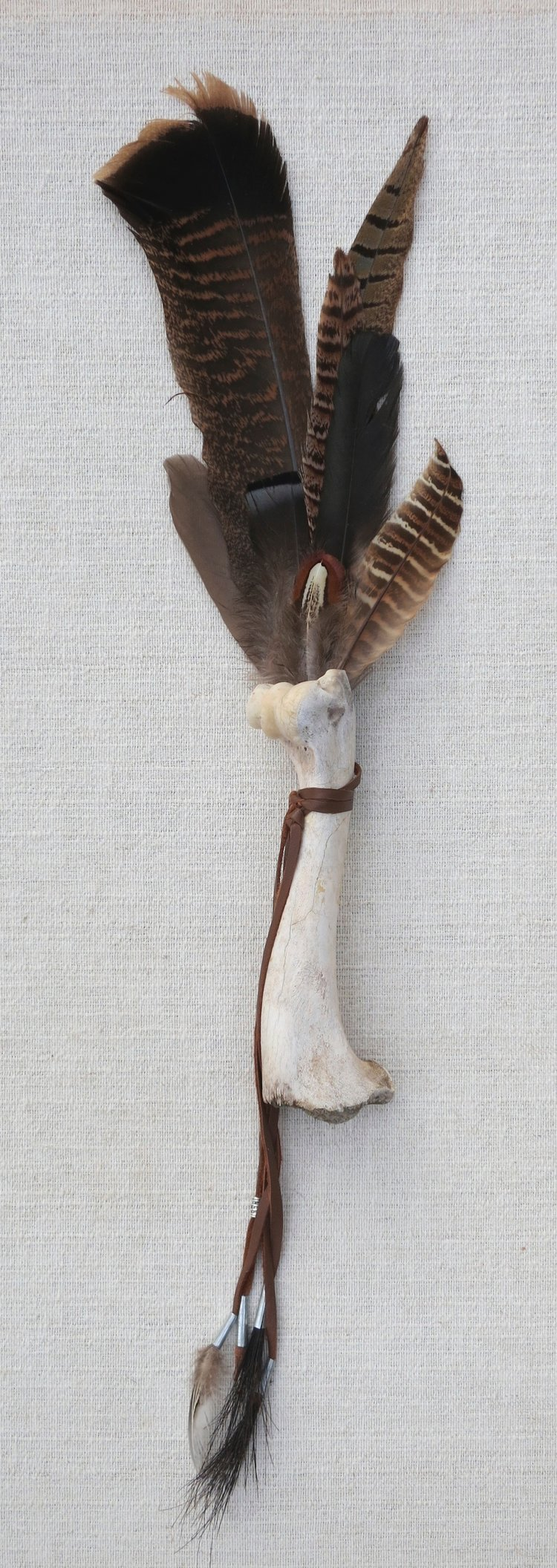 "Tribute #7  2014 25"" Found feathers, deer bones assembled with  leather, tin and horsehair."