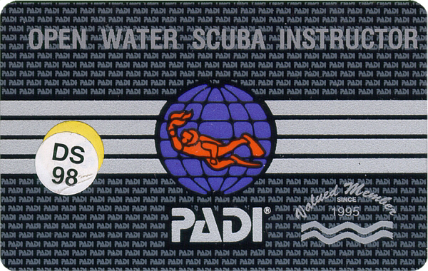 A black PADI open water scuba instructor certificard card that is earned with coconut tree divers.