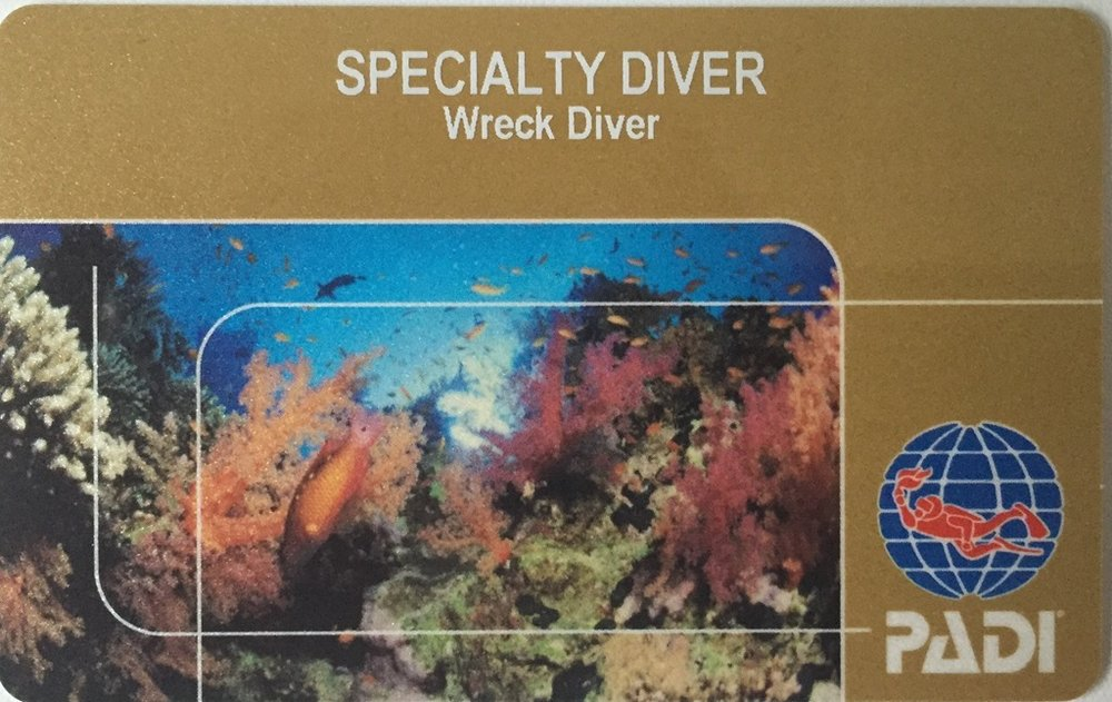 a PADI wreck diver specialty certification card with coconut tree divers, and a reef and padi logo on the card.