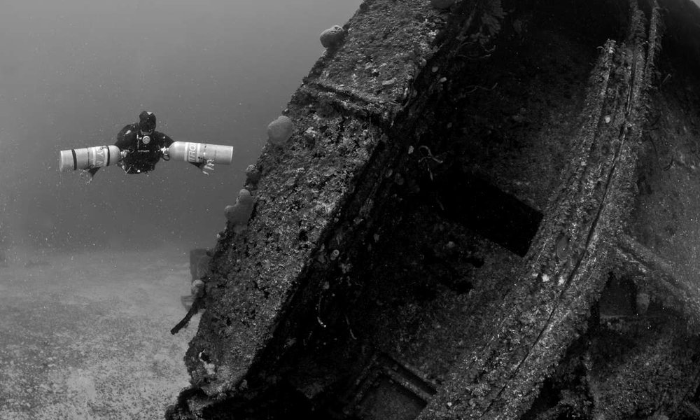 a sidemount diver along side a wreck in roatan