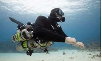 A coconut tree diver in a technical / sidemount diver configuration on a sandpatch in roatan at the divesite lighthouse.
