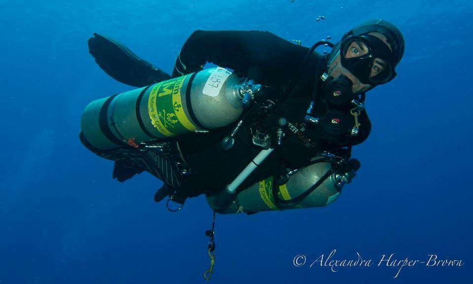 a TDI / PADI sidemount diver with the roatan tec center that operates out of coconut tree divers in the blue caribbean water is reaching behind him to adjust a sidemount tank.