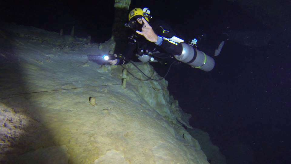 a PADI / TDI technical sidemount diver in a cave at the divesite hole in the wall, he is following a coconut tree dive instructor that has layed down the guideline.