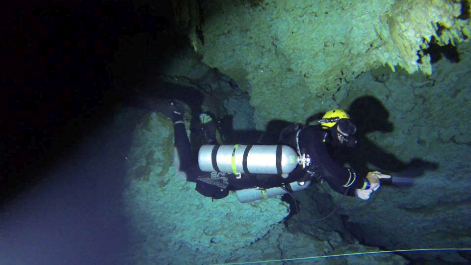 a tec 40 diver in a PADI / TDI sidemount Xdeep sidemount configuration diving in a cave at the divesite Texas.  He is following a dive instructor from coconut tree divers.