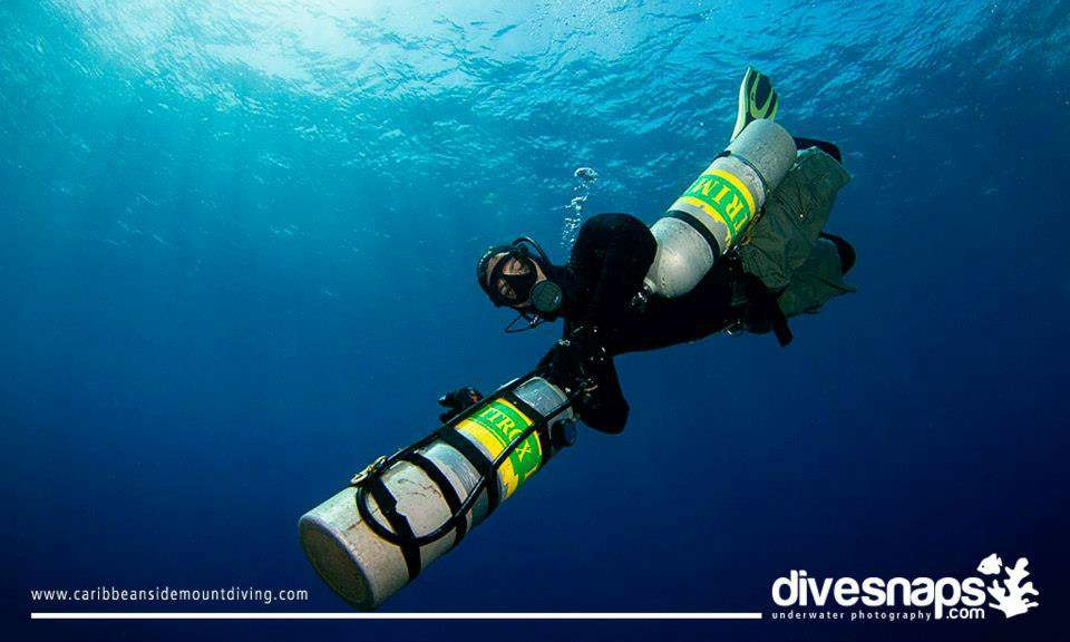 a sidemount tec 50 diver performing a skill with roatan tec center and coconut tree divers in roatan, he is holding out one tank.