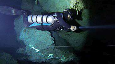 a PADI / TDI techncial sidemount diver in the Xdeep configuration is swimming along side the cave line.